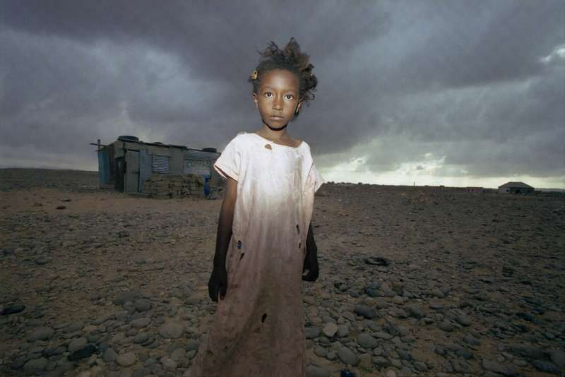A young girl crosses the barren wasteland to reach Shebele B camp on the edge of Bossaso. Once a thriving port, Bossaso is now surrounded by sprawling camps overflowing with displaced people from across the Horn of Africa.