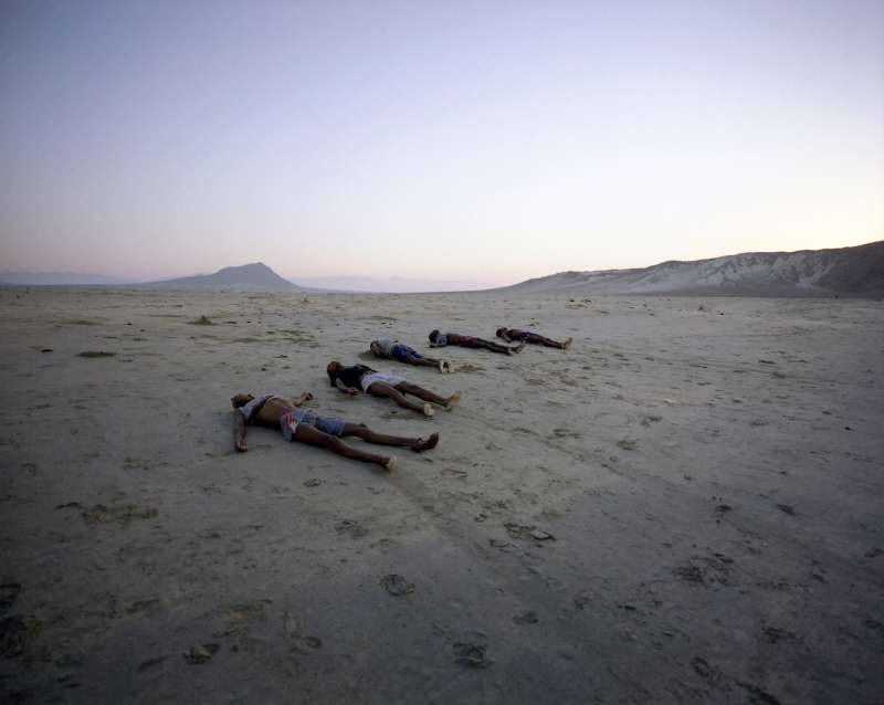 A row of corpses line Al-Bedha beach at dawn. Following the arrival of a group of 365 refugees by boat the previous night, 34 corpses were washed ashore - either beaten to death by smugglers or drowned offshore.