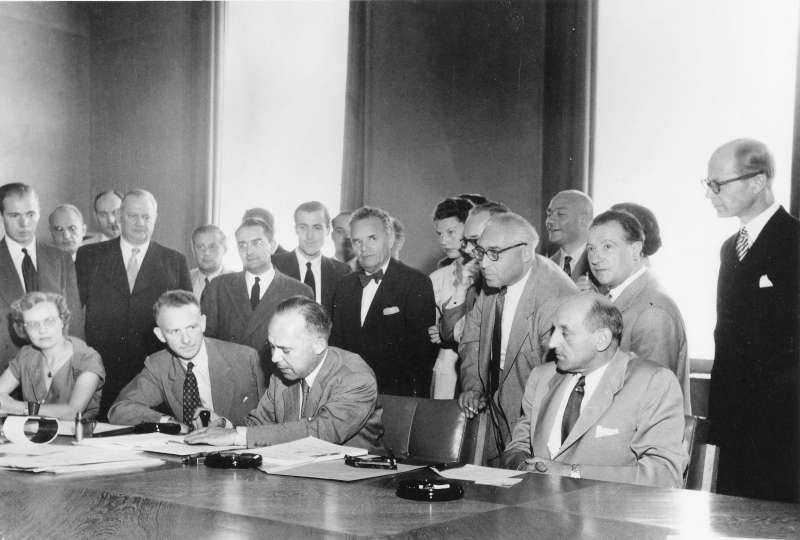 Signature of the 1951 Refugee Convention in Geneva, Switzerland /the three seated men (l-r): Mr. John Humphrey, Director of the Human Rights Division; Mr. Knud Larsen (Denmark) President of the Conference; Dr. G.V. van Heuven Goedhart, High Commissioner for Refugees /  copyright Arni / UN Archives / August 1, 1951