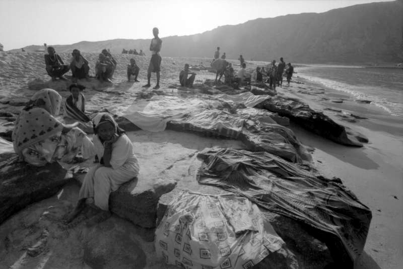 Gathered on Al-Bedha beach at dawn, Ethiopian refugees who arrived during the night lay out their clothes to dry on rocks. They were dumped by the smugglers nearly a kilometre from shore after being fired upon by Yemeni troops.