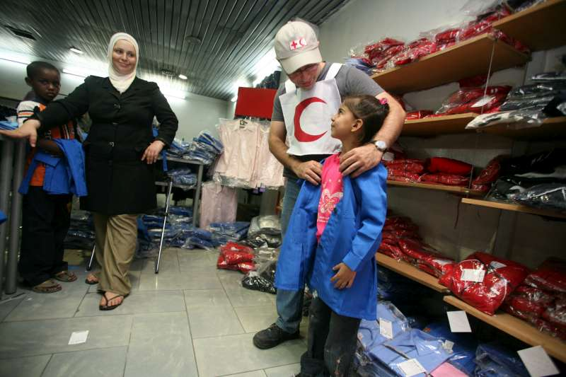 Syria / Iraqi refugees / A Red Crescent volunteer helps a young Iraqi find a school uniform in the correct size. To encourage poor Iraqi families to register their children in school, UNHCR plans to provide financial assiance, uniforms, books and school supplies to Iraqi refugees registered with UNHCR. /2007
