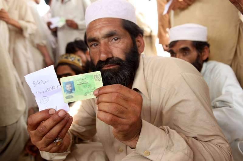 Pakistan / Sheikh Yasin camp / An IDP man shows his national ID card and names before being assigned a UNHCR-WFP ration card which will allow him and his family to have access to assistance in the camp. UNHCR and the government have established 89 registration points in NWFP. 1.4 million people have been displaced since May 2, following fighting between governmental troops and Talibans in the Swat, Lower Dir and Buner districts. / Mardan district, May 17, 2009