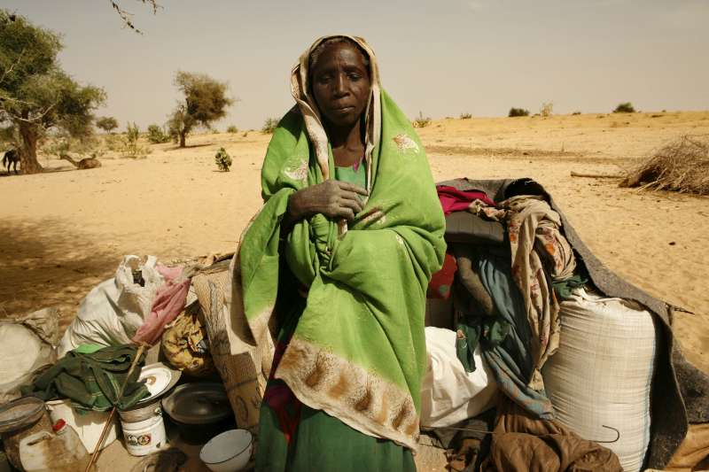 A newly arrived refugee from the Darfur region of Sudan rests next to her belongings in Seneit, Birak area, eastern Chad.