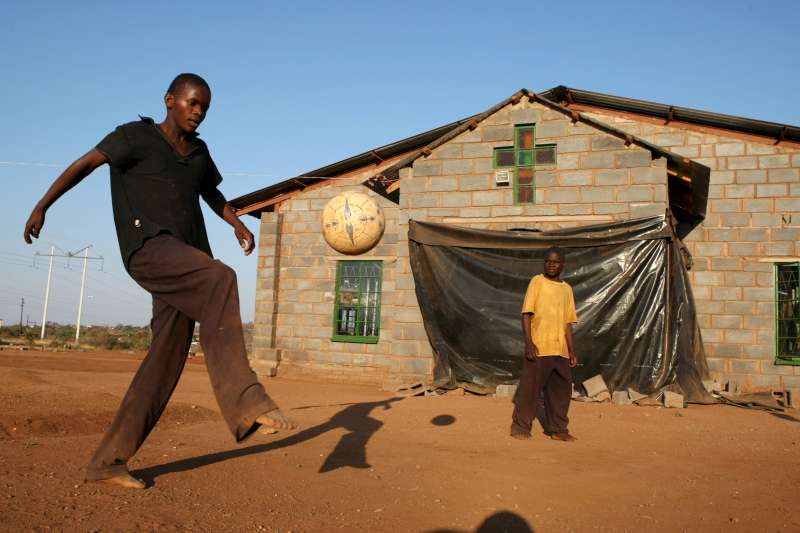 Teenager Conwell plays football at the Boy's Shelter in Nancefield, Musina, South Africa. The shelter houses more than 200 boys aged up to 16. Most of the boys crossed the border unaccompanied. They are given food, shelter and lessons.