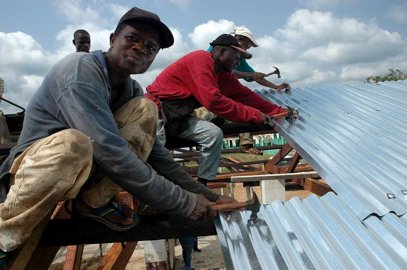 Through a special community empowerment project, these displaced people are building a school, and a roof for the market place in Gbarlatuah Town, Bong County, Liberia.