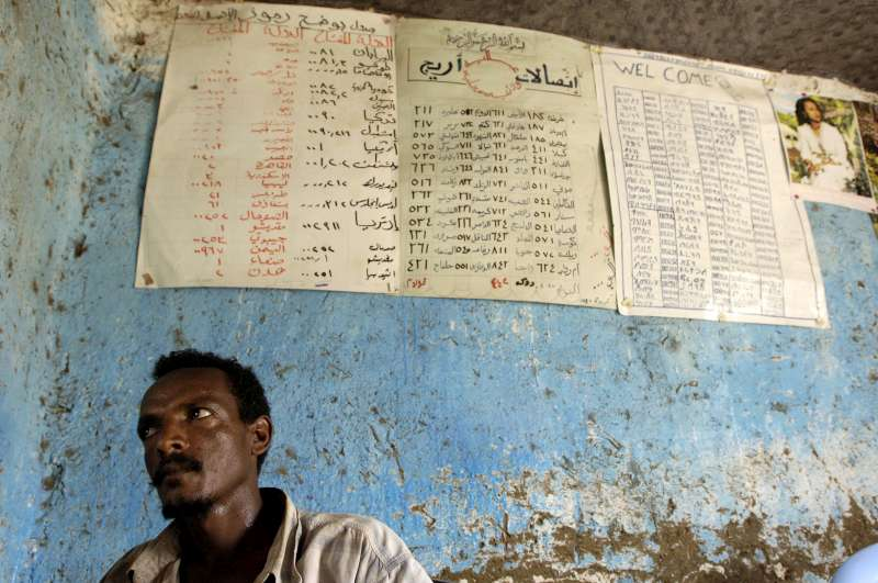 An Eritrean refugee waits to make a call at a telephone bureau in Kilo 26 refugee camp. On the wall behind him are the call rates for countries around the world.