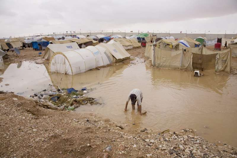 A Palestinian man wades through flood water in search of lost belongings. Severe rainstorms in October 2008 left tents inundated with water and sewage at Al Tanf, a settlement in the narrow no man's land between Iraq and Syria.