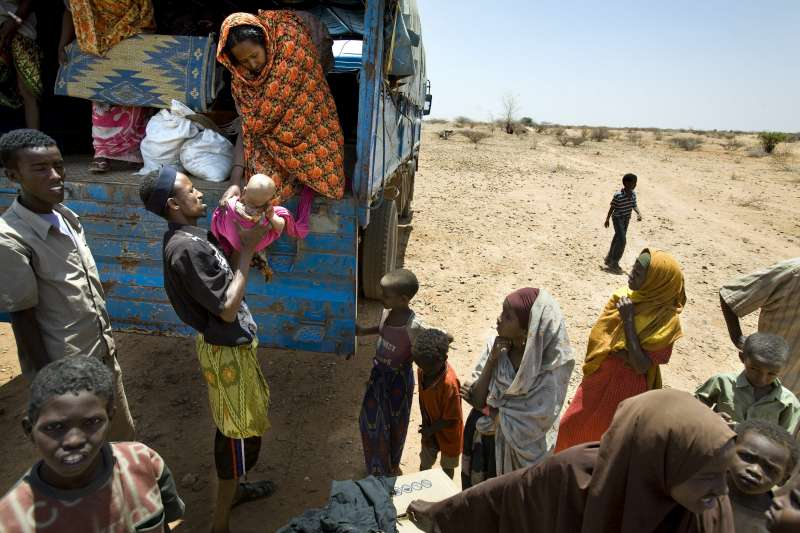 Newly arrived Somali refugees and their belongings are trucked […]