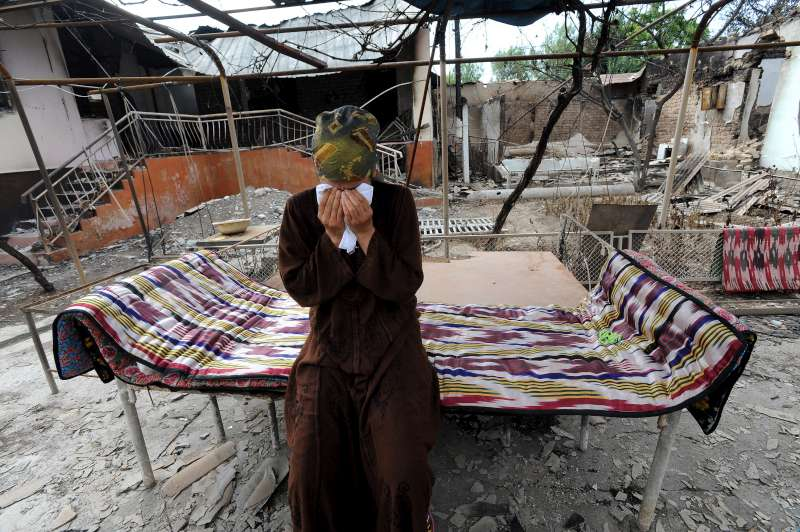 Mansura sits in the remains of her family compound, which was destroyed during the recent violence.