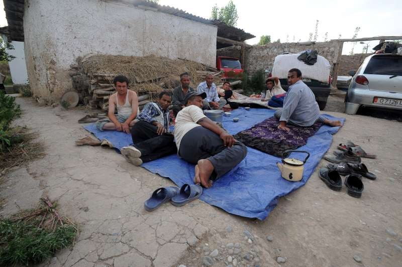 A group of men share a plastic sheet. Many of the displaced in Kyrgyzstan have no shelter or blankets and must sleep in the open.