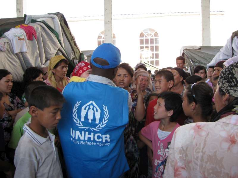 A UNHCR staff member talks to refugees in Pakhtaabad refugee camp, in the Andijan province of Uzbekistan. The camp, established in a former warehouse.