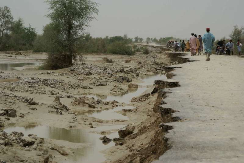 Residents walk on a flood-ravaged road outside Tali village in Balochistan.