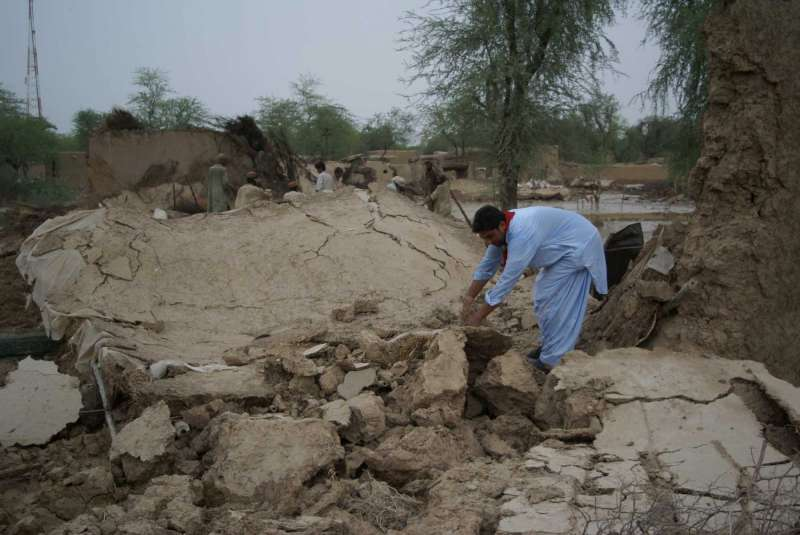 A man in Balochistan digs through the rubble in search of personal belongings to salvage.