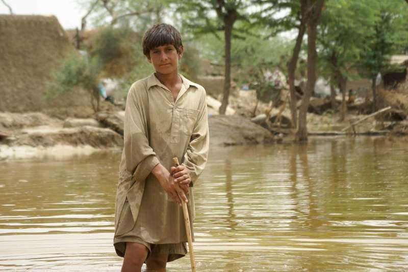 A young boy feels his way through flood waters using a walking stick.