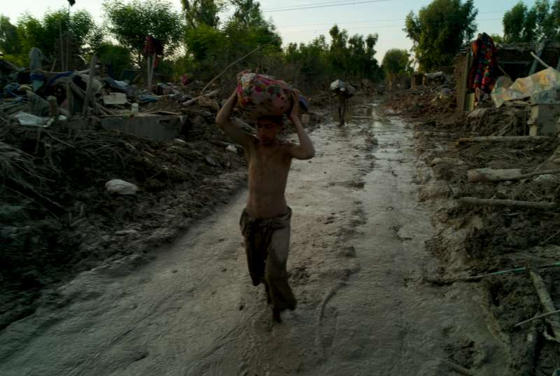 A boy makes his way through thick mud and debris carrying belongings he managed to salvage from his family's home, Pir Pai.