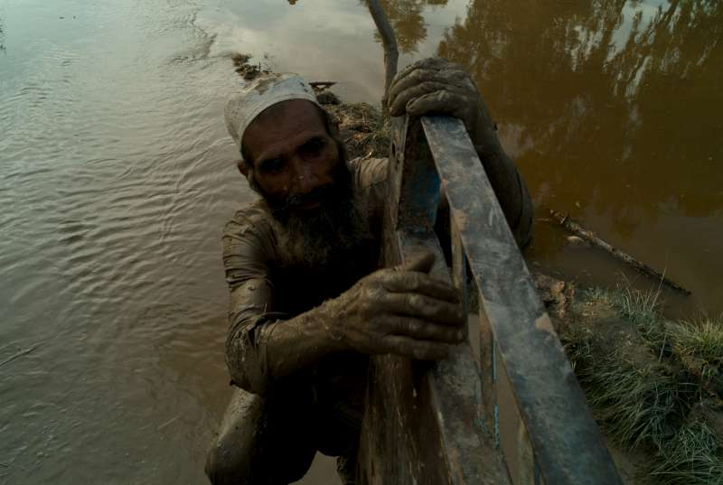 Afghan refugees salvage their belongings from the mud.