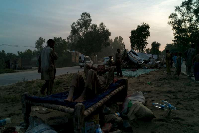 A man surrounded by salvaged goods rests in an impromptu camp on a median strip of the Grand Trunk Road, near Nowshera.