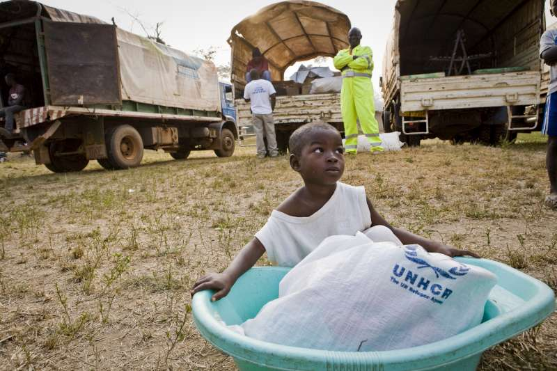 A small girl waits to board a UNHCR truck that will take her […]