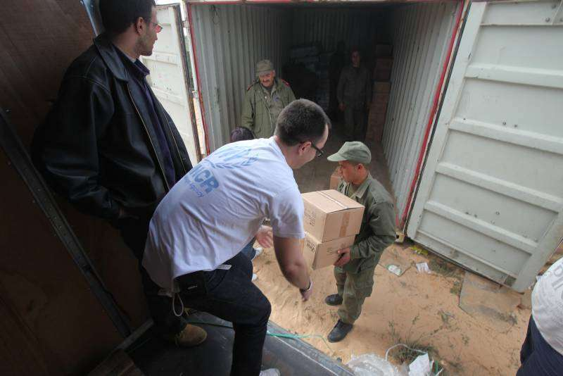 UNHCR staff help unload relief items at a transit camp near the Tunisia-Libya border.