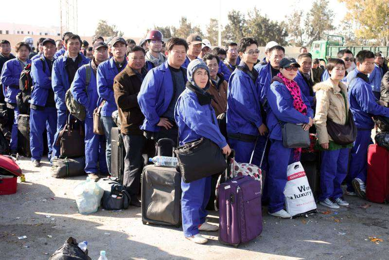 A group of Chinese workers queue to get into Tunisia.