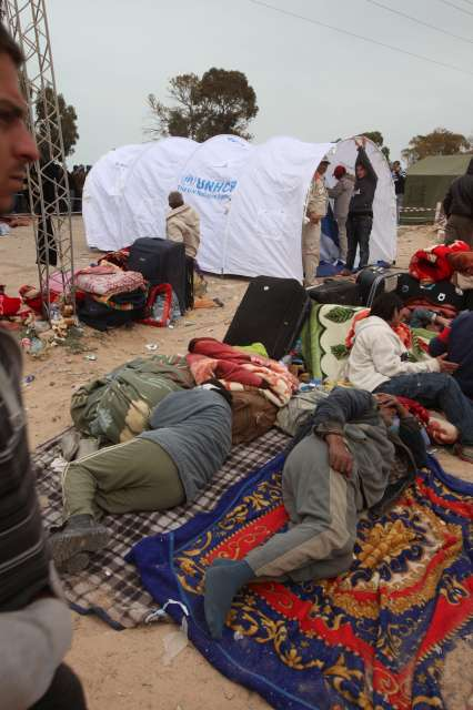 Exhausted by their ordeal in fleeing Libya, these people try to sleep while their tent is put up.