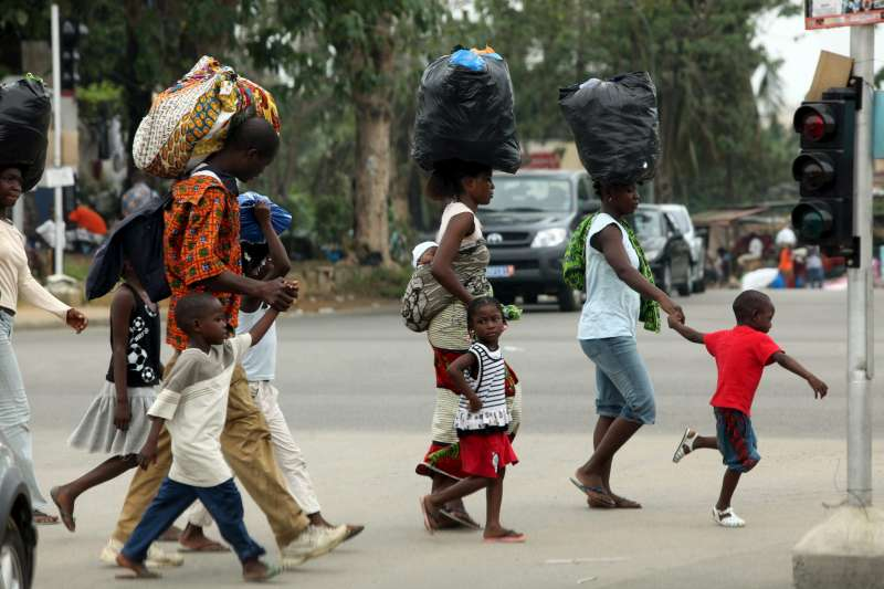 A family hurries away from the Abobo neighbourhood in search […]