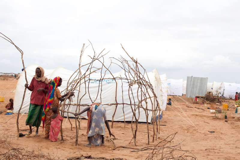A family relocated to Ifo Extension builds a tukul next to their new tent to shield against the mid-day sun.