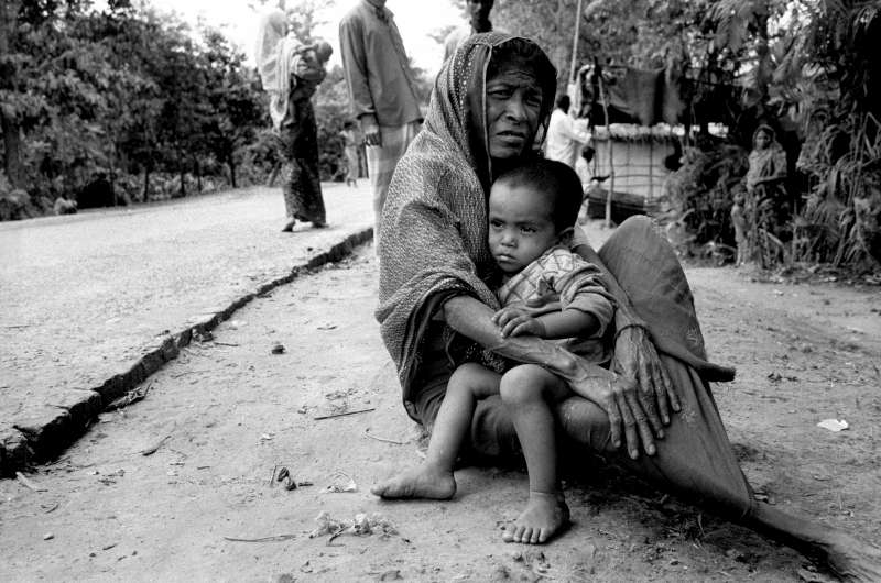 Thousands of the Muslim Rohingya refugees in Bangladesh have not been registered and have received little assistance. A woman sits on the side of the road with her grandchild at the old Tal Camp near Teknaf. The government has since relocated the camp residents to a safer and less congested area.