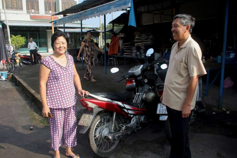 "New Vietnamese citizen Tran Hoang Phuc, whose new name means ""Golden Happiness"", and his wife next to his motorbike in the southern town of Cu Chi. During the 35 years the former Cambodian refugee was stateless, he could not even legally buy a motorbike because he was not a citizen."