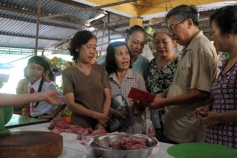 "New Vietnamese citizen Tran Hoang Phuc, formerly stateless for 35 years, goes shopping in the market with his wife. He is surrounded by other formerly stateless people, who all got their Vietnamese citizenship in July 2010. They now have red ""family books"", the crucial document for all official transactions between citizens and the government in Viet Nam. But the new citizens are full of questions for him – a longtime refugee leader from Cambodia – about exactly what rights it confers."