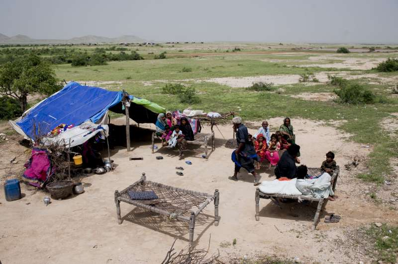 A family of flood survivors sets up camp with salvaged items from their ruined homes in Thatta district.