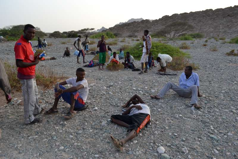 Exhausted new arrivals recover on the Al Hamra'a coast in southern Yemen. Smugglers often force their passengers to jump into deep water hundreds of metres from shore, for fear of being shot at by the coastguard. Many die because they cannot swim or are weak from the trip.
