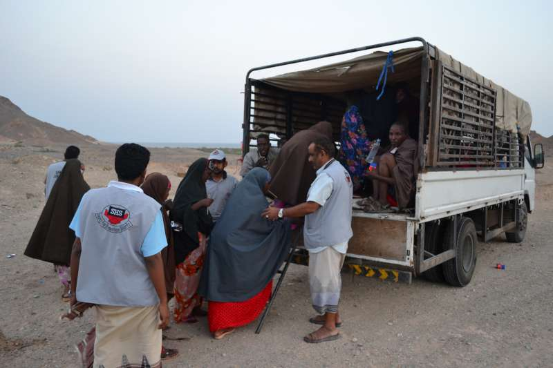 People are helped into trucks for transport to Mayfa'a Hadjar Transit Centre, where they will receive food, a place to sleep and medical care.