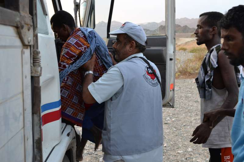 SHS staff help people into a truck that will take them to the Mayfa'a Hadjar Transit Centre.
