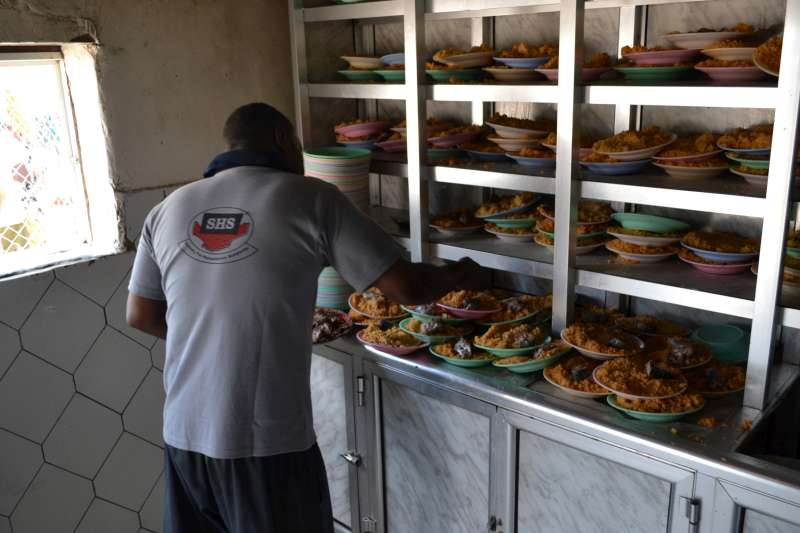 Plates of food are prepared for new arrivals in the Mayfa'a Reception Centre.