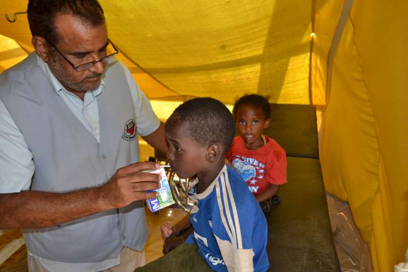 The director of SHS, Nasser Salim Ali Al-Hamairy, gives milk to newly arrived children in Mayfa'a Hadjar Transit Centre.