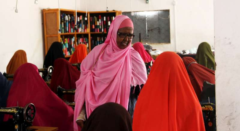 "Mama Hawa Aden Mohamed oversees a tailoring class at the Galkayo Education Centre for Peace and Development (GECPD) in Somalia. The seamstresses produce reusable ""dignity"" kits, consisting of underwear that will be distributed with homemade pads. These are given to displaced women and refugees around Galkayo and further afield."