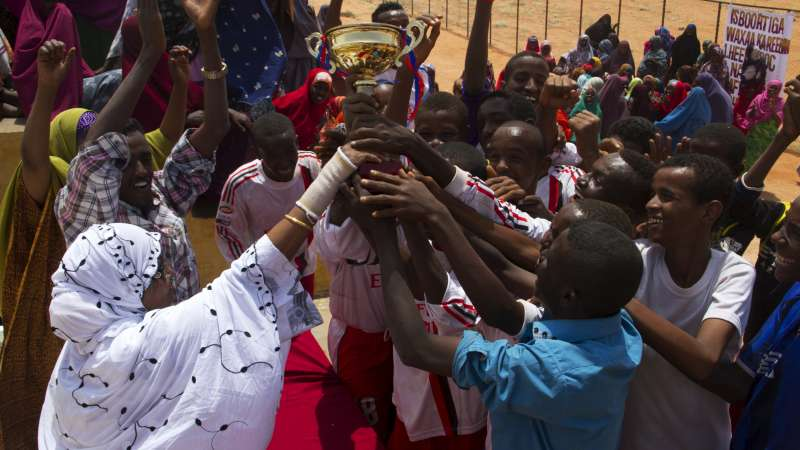 Mama Hawa hands a trophy to the winning team in a football tournament. The GECPD offers vocational training for boys, and provides food and non-food relief to the displaced.