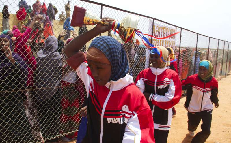 The victorious women's basketball team parade with a trophy before jubilant supporters at the training centre Mama Hawa established in Galkayo, Somalia.