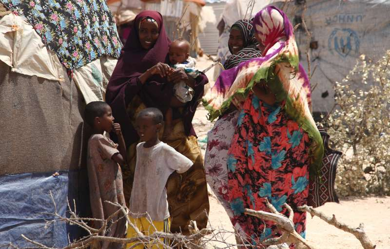 IDP women and children gather outside their makeshift homes at the Halabokhad settlement in Galkayo.