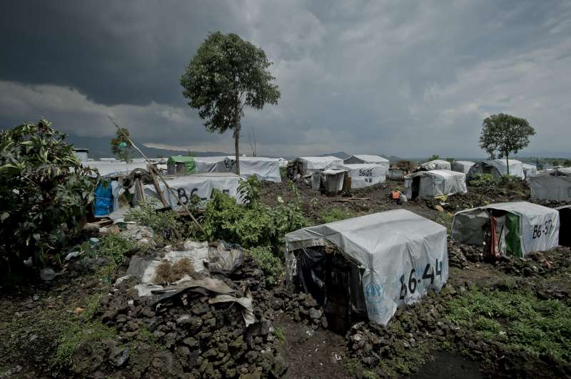A view of some of the shelters at Mugunga III under a dramatic sky. The camp is located to the west of Goma, capital of North Kivu province. It was providing shelter to about 14,000 people when the rebel M23 movement began to advance on Goma in mid-November. Thousands more fled there.