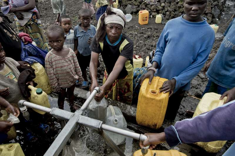 Eugenie, Sukuru's mother, fills her jerry can with water.