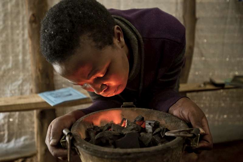 Yvonne, aged 18, blows on live embers before cooking a meal in her shelter in Rwanda's Kigeme camp. She is a refugee but she has been attending classes to prepare her for the Rwandan curriculum. She's experienced a lot of unpleasant things, including the trauma of flight, but she remains hopeful about the future.