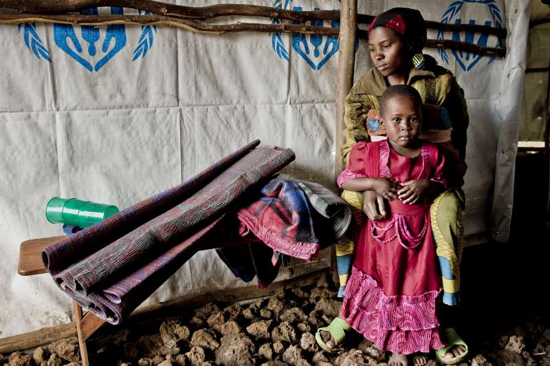 The exhausted Izabayo holds her daughter in the reception tent in the Nyakabande Transit Centre. The 25-year-old new arrival was given a sleeping mat, blankets, soap, cup, plates and a range of other assistance. She was waiting to be given room in a tent with her two children.