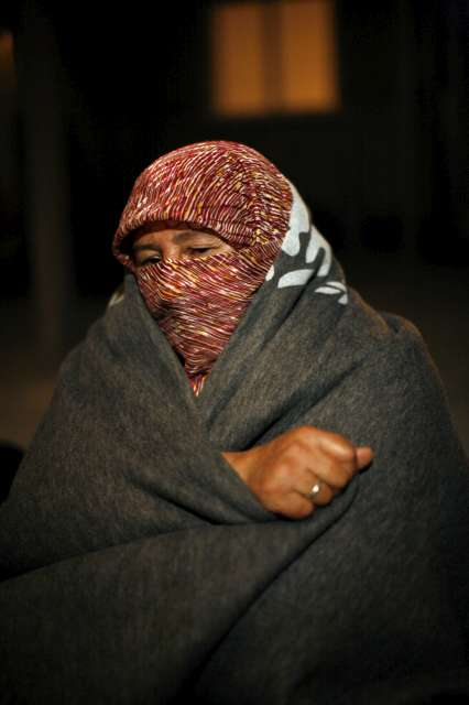 A Syrian woman wraps up against the cold shortly after arriving […]
