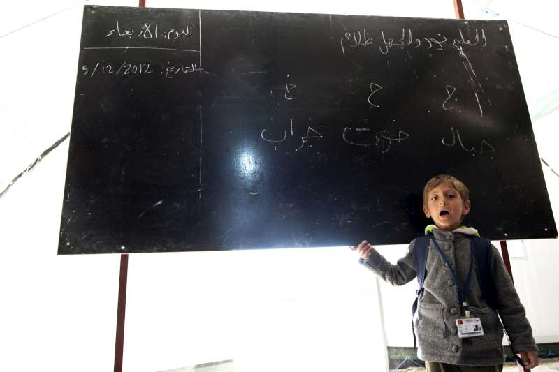 A Syrian refugee boys stands in front of a blackboard while attending […]