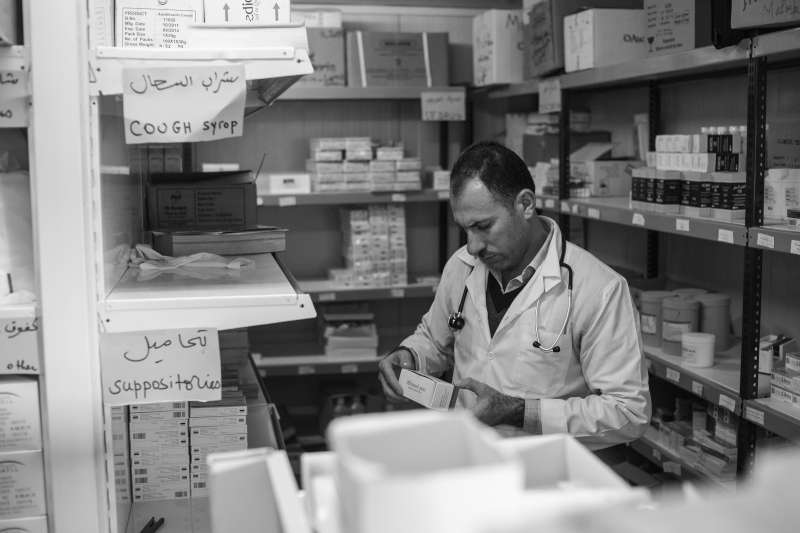 Dr. Hassan checks a box of medicine in the pharmacy of the Médecins Sans Frontières clinic in Domiz Refugee Camp.