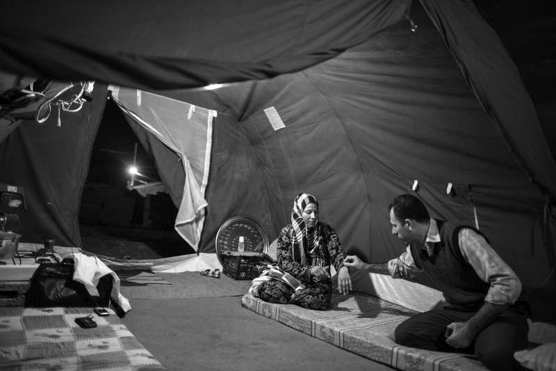 In the evening, after completing his duties at the camp clinic, Dr. Hassan visits a family in their UNHCR tent to check on a woman he has been treating.