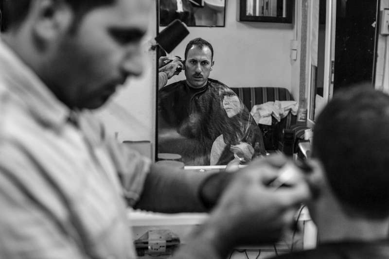A Syrian barber gives Hassan a shave in Domiz Refugee Camp. Many refugees and a growing number of locals frequent the small businesses that operate in the camp. Some refugees work as barbers or tailors, others sell everything from cell phones to fresh fruit and vegetables.