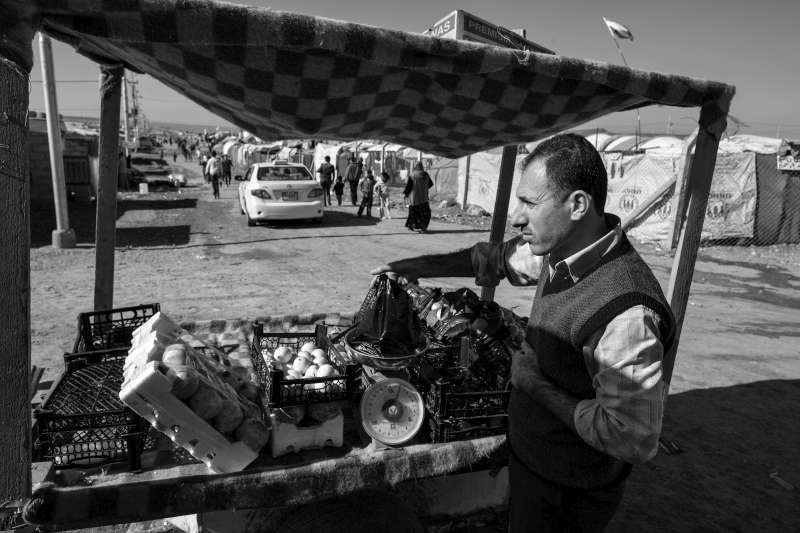 Dr. Hassan shops for his family at one of the many stalls selling fresh fruit and vegetables in Domiz Refugee Camp.